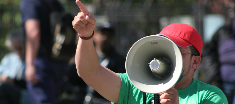 Protester pointing finger and holding megaphone